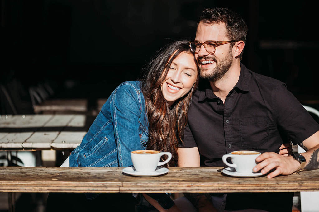 woman leaning on man's shoulder at coffee bar