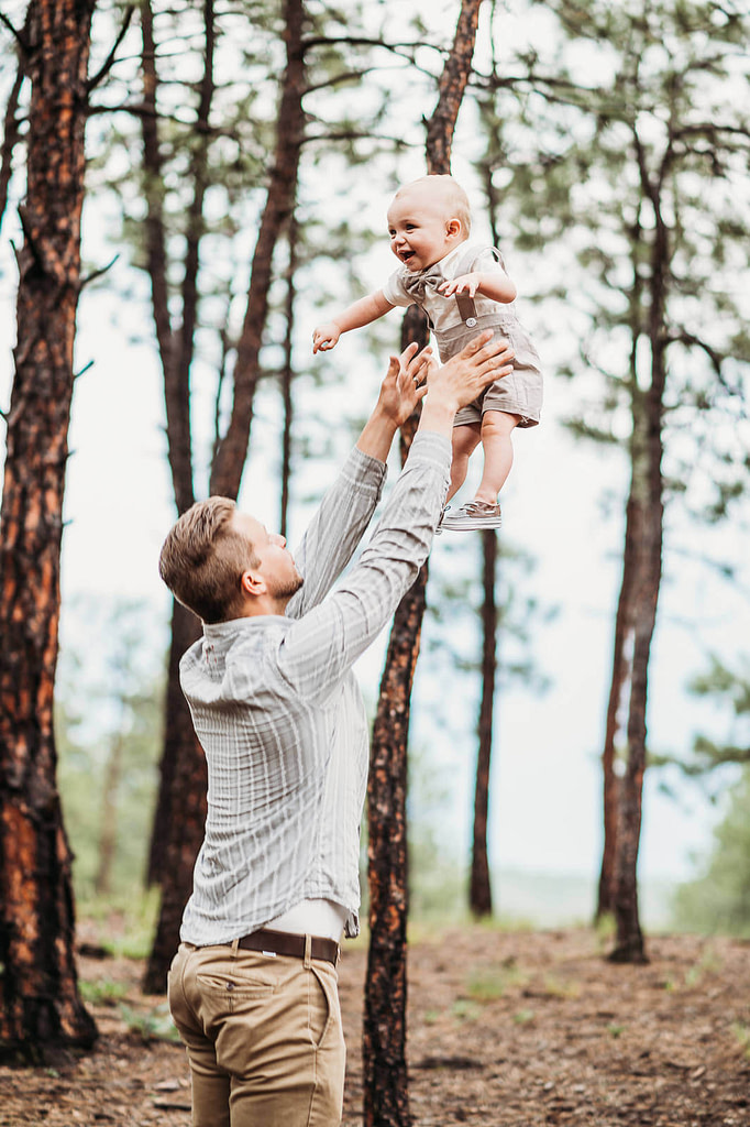 father holding baby boy with arms outstretched