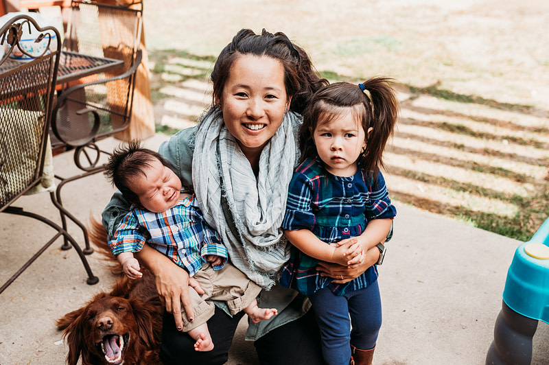 asian mom holding grumpy asian toddler and crying baby with silly dog