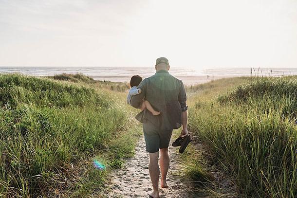 father holding daughter walking toward ocean