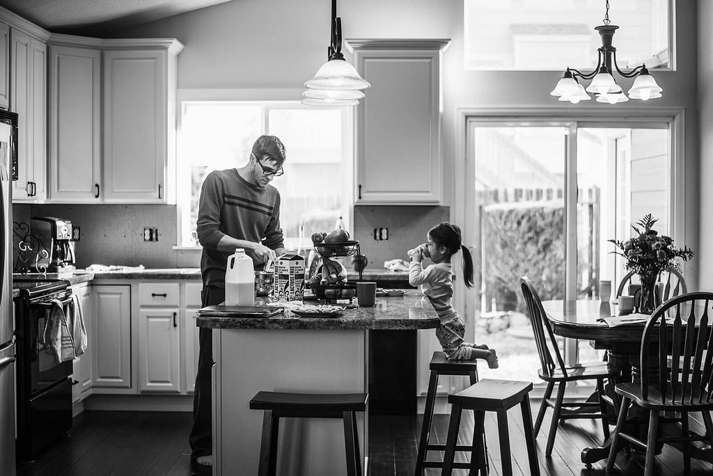 little girl sits on kitchen stool as dad fixes breakfast