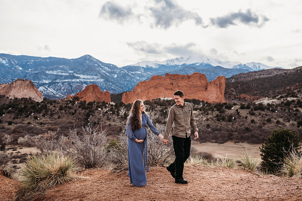 Man leading Pregnant woman in from of pikes peak and garden of the gods