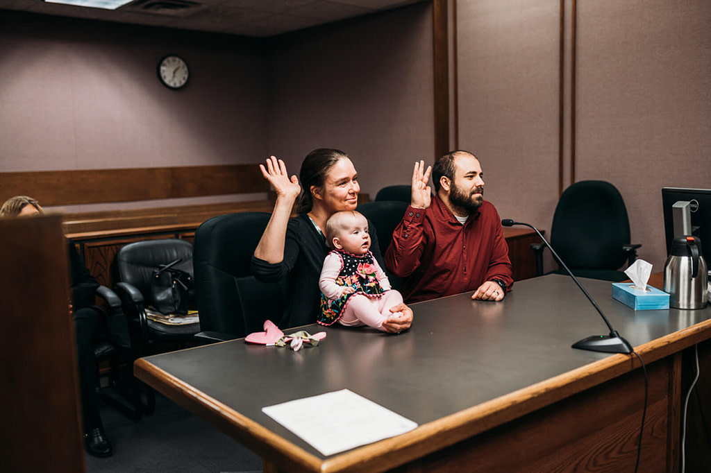 man and woman hold their hands up for court oath