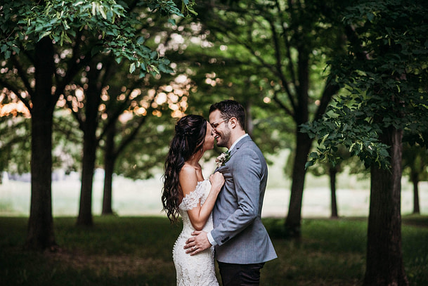 bride and groom kissing with trees in background