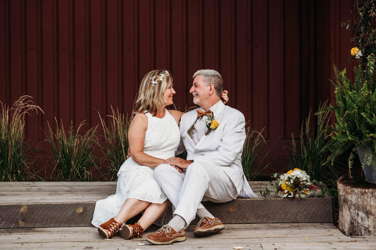 bride and groom sit on concrete step