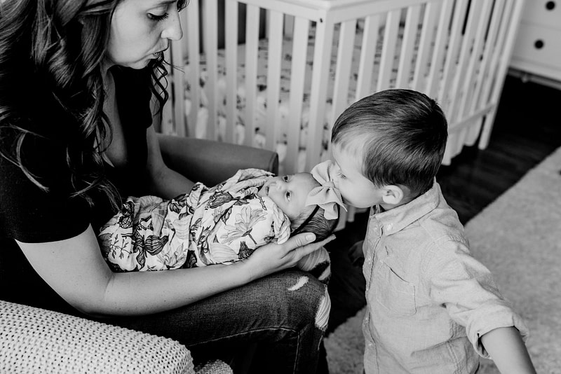 mom holding baby girl while brother kisses his sister's forehead